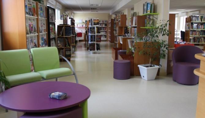 Espaces de la médiathèque. fauteuils verts et tables basses violettes