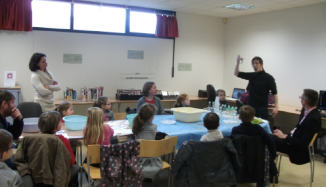des enfants autour d'une grande table écoutent les instruction d'un animateur