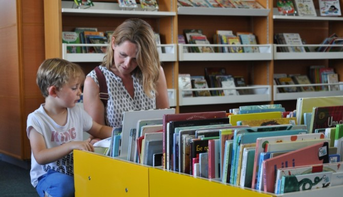 mère et fille cherchant des albums dans un bac jaune