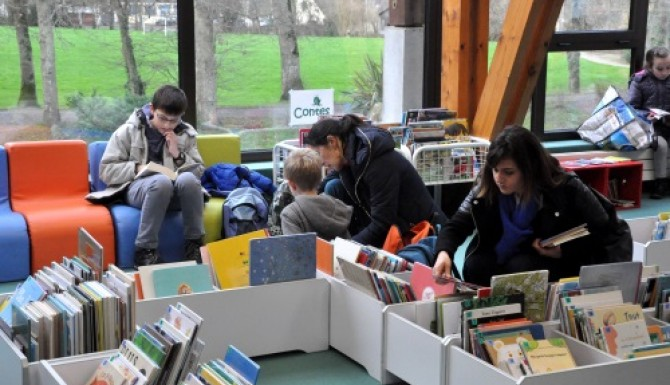 étage dédié à la jeunesse. Enfants lisant sur des banquettes confortables. Bacs au sol pour les albums