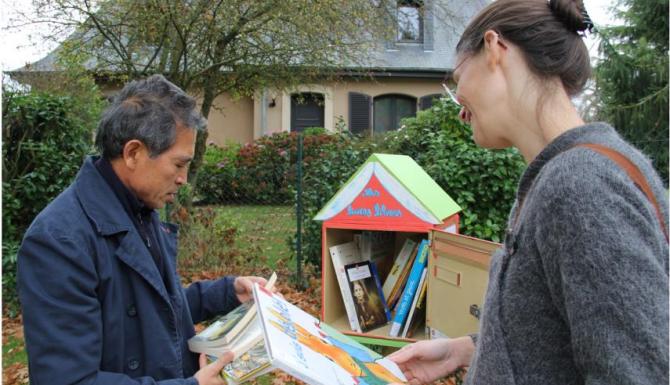 une bibliothécaire réalimente une boite de dons de livres tandis qu'un citoyen consulte un ouvrage déposé
