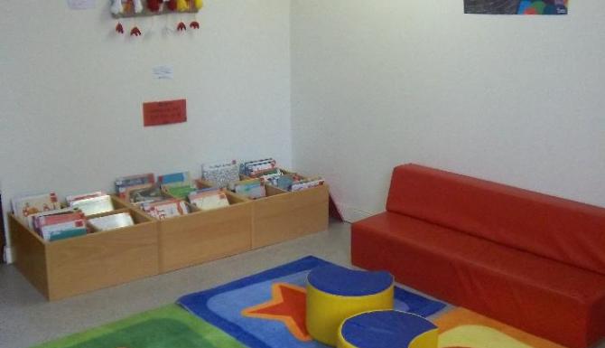 espace des enfants, tapis de couleurs et assises rouges. Bacs d'albums autour de cet espace