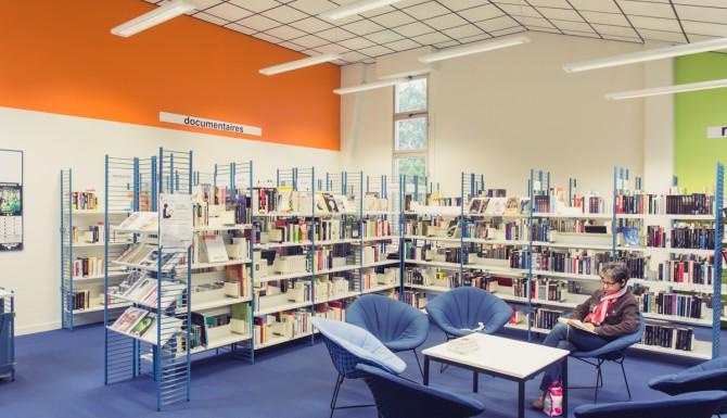 coin des documentaires, rayonnages et espace central de lecture (fauteuils et tables basses)