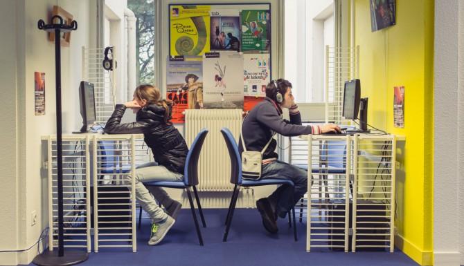 coin multimédia, deux adolescents dos à dos, chacun à son ordinateur