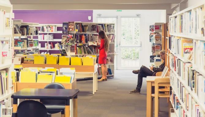 espaces de la bibliothèque. Mur du fonds violet, des bacs, des fauteuils, des tables et des rayonnages