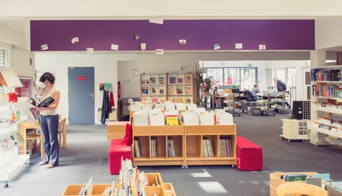 plan large de la bibliothèque, mur du fonds violet, on y voit les espaces avec leurs mobiliers et des usagers. Au fonds, on aperçois l'accueil
