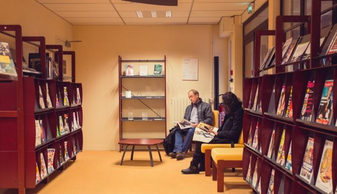 Presse et romans dans des rayonnages, personnes assise lisant des documents