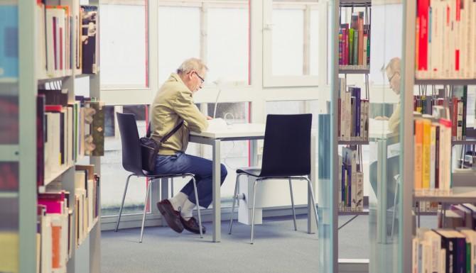 une personne assise à une table est en train de lire
