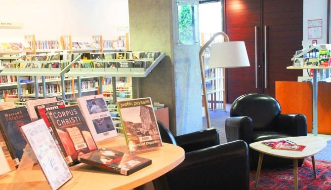 Table de présentation et coin lecture (fauteuils, table basse et liseuse).