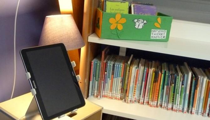 tablette numérique en libre accès en jeunesse. Ena rrière-plan on distingue des livres