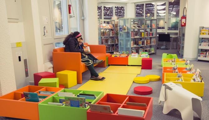Espace enfants, très coloré. Banquette orange, tapis et bacs de toutes les couleurs. Un siège en forme d'éléphant