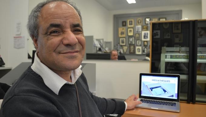 Portrait d'Abder ragui devant un ordinateur portable affichant l'accueil d'une portail des médiathèques de Rennes métropole