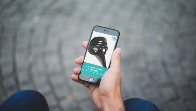Vue du dessus d'une personne lisant un livre numérique sur un Iphone