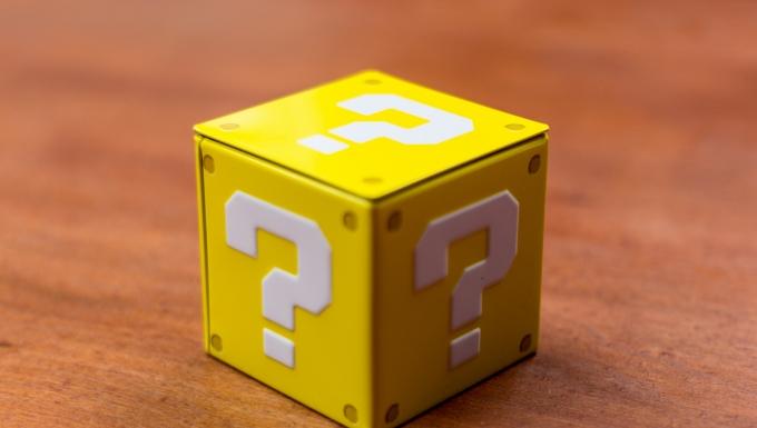 Carré jaune dont chacune des faces est marquée d'un point d'interrogation de couleur blanche.