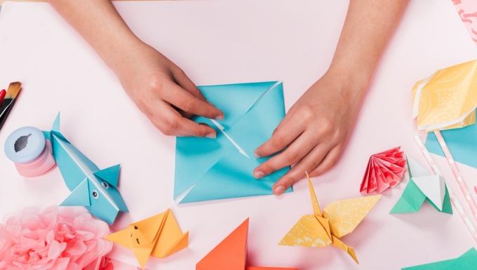 Une personne réalisant des origamis.