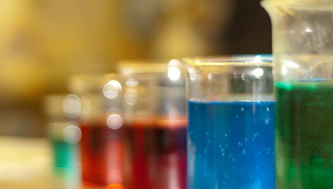alignement d'éprouvettes contenant des liquides de couleurs. Du premier-plan à l'arrière-plan : vert, bleu, rouge, rouge, vert