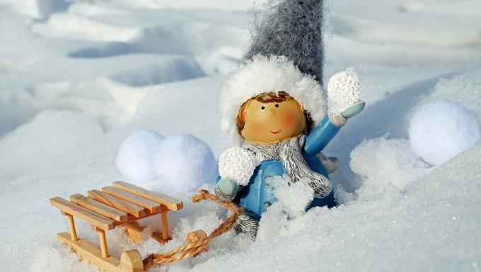 petit personnage trainant une luge dans la neige