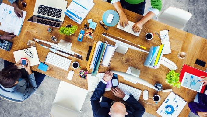Plusieurs personnes réunies autour d'une table de travail (vue de haut). Disposés sur l'espace de travail des ordinateurs, documents, dossiers et fournitures.