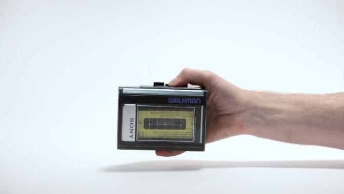 Une main tenant un baladeur Walkman de la marque Sony.