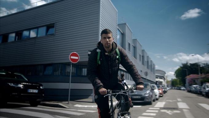 Un livreur roulant à vélo.