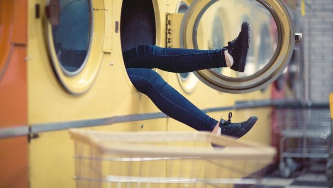 Les pieds d'une personne tombée dasn une machien à laver dans un lavomatique.