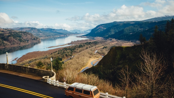 vue d'un paysage américian représentant les grands espaces. Un mini-van en premier plan représente le voyage. Au loin on voit un fleuve et de hautes montagnes