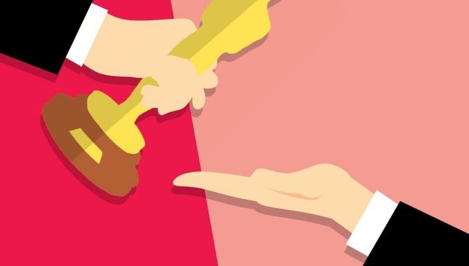 Une main remet à une autre main la statuette des Oscars