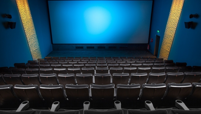 Salle de cinéma vide photographiée du denrier rang.