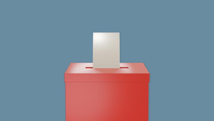 Un bulletin de vote introduit dans une urne.