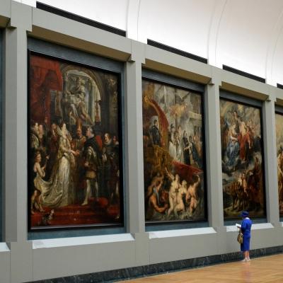 Une personne devant des tableaux dans une galerie du Musée du Louvre.