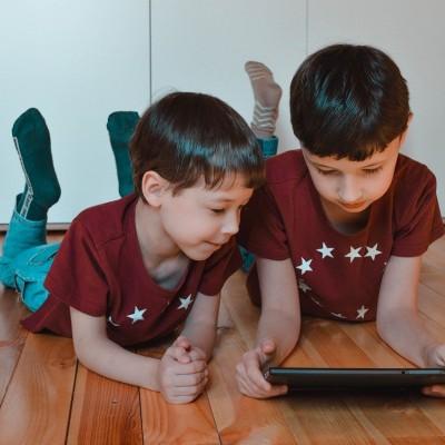 Deux enfants allongés par terre avec une tablette