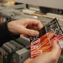 Rayonnage de disques de la Bibliothèque des Champs Libres avec un agent effectuant le rangement de documents.