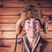 Homme coiffé d'un bonnet en fourrure de castor, souriant