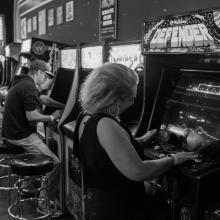 Salle d'arcade, bornes et personne jouant à des jeux divers