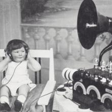 Photo en noir et blanc d'un enfant écoutant avec un casque un poste radio dans les années 30.