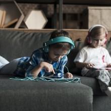 Deux enfants dans un canapé avec tablettes et casques audios