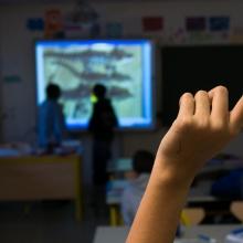 Main levée d'un élève dans une salle de classe pour répondre à une question