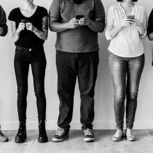 Photo en noir et blanc de personnes consultant leur téléphone portable.