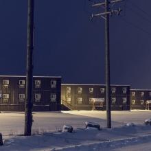 3 immeubles sous la neige vus de nuit.