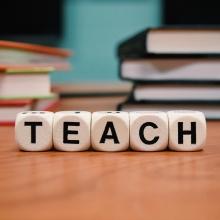 """Dés marqués d'une lettre formant le mot """"Teach"""" sur un bureau d'une salle de classe"""
