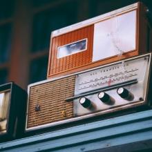 Des postes de radio anciens empilés les uns sur les autres sur une étagère.