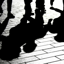 Photo en noir et blanc de personnes démabulant dont les ombres se reflétent au sol.